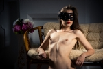 sexy nude model wearing a mask in a beautiful interior